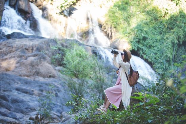 Turista femenina que está mirando los prismáticos para ver la atmósfera en la cascada