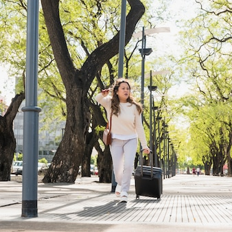 Turista femenino joven que tira de su bolso del equipaje que intenta pedir un taxi