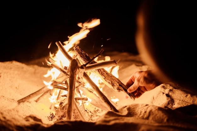 Turista hace un fuego en la playa.