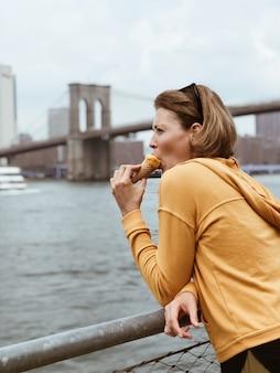 Turista hermosa mujer comiendo un cono de helado. bastante joven come postre. concepto de comida de vacaciones