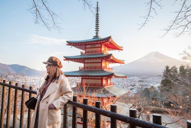 Turista hermosa de la mujer que sonríe en la pagoda de chureito y la montaña de fuji, japón