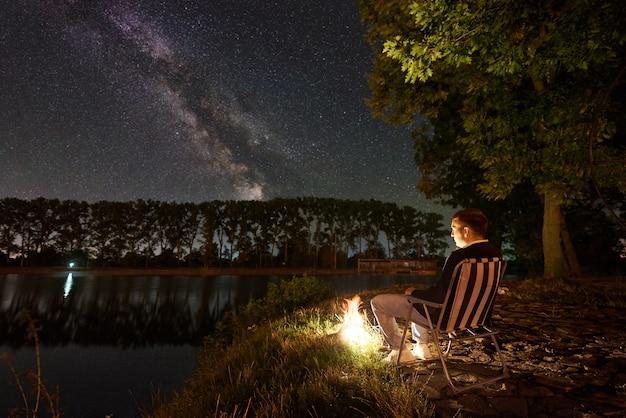 Turista hombre descansando sentado en una silla en la orilla del lago por la noche