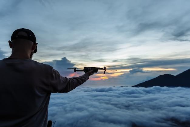 El turista del hombre mira la salida del sol en el volcán batur en la isla de blai en indonesia. hombre caminante lanzando un avión no tripulado volador con un control remoto en la mano, concepto de viaje