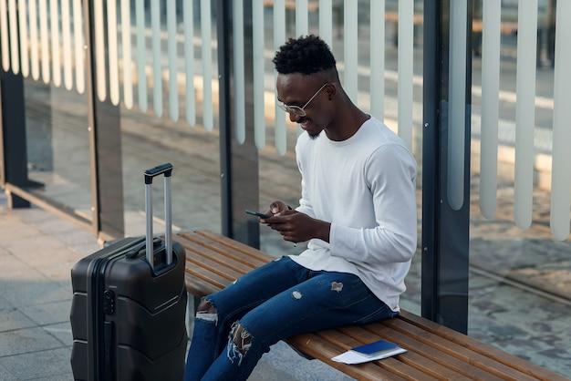 Turista joven barbudo con mochila y teléfono inteligente se sienta en la parada de transporte público y espera el tranvía en el centro de la ciudad
