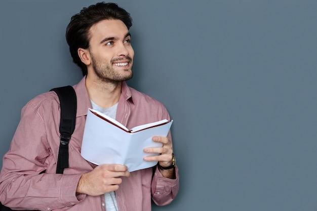 Turista joven. buen hombre guapo positivo leyendo un guía turístico y sonriendo mientras planea su próximo viaje