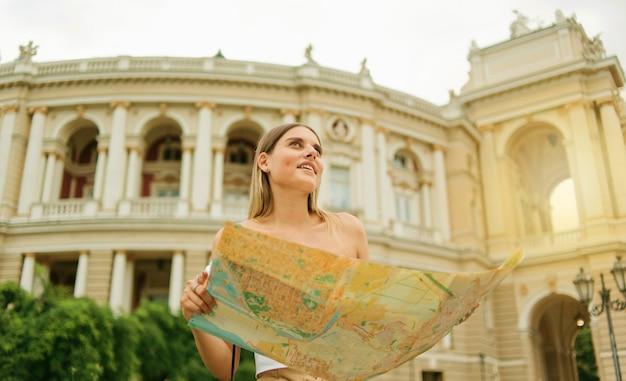Turista joven, carismática tiene en sus manos mapa de la ciudad