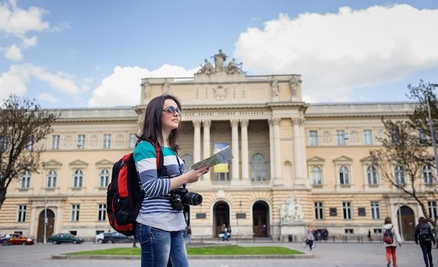 Turista joven con mapa y cámara