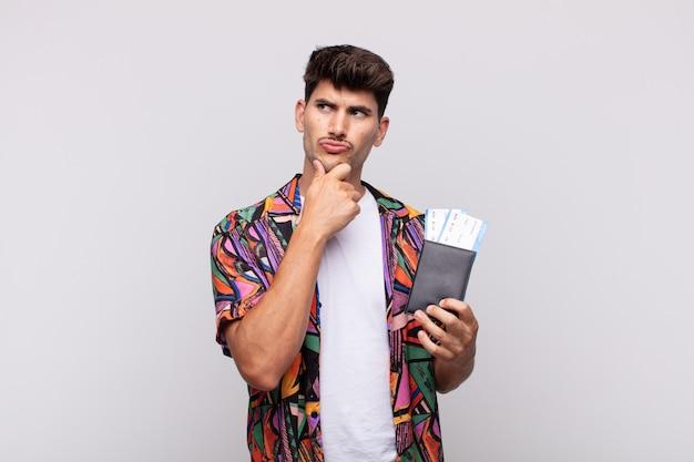 Turista joven con pasaporte pensando, sintiéndose dudoso y confundido, con diferentes opciones, preguntándose qué decisión tomar