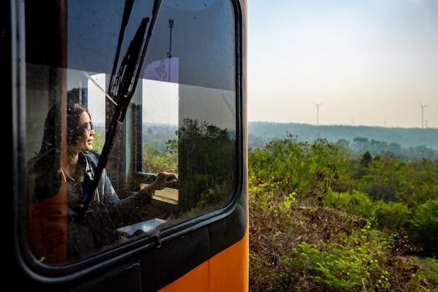 Turista lindo de las mujeres que sonríe y que mira en la ventana del tren por tiempo del viaje del verano