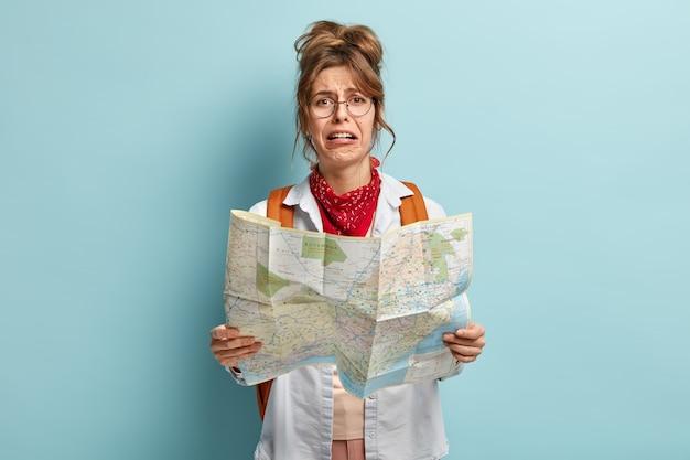 Turista llorando perdida en un destino desconocido, sostiene un mapa, trata de encontrar el camino, mira con expresión abatida insatisfecha, usa anteojos redondos, tiene mochila con cosas empaquetadas, se para en el interior