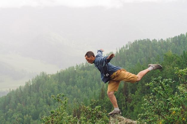 Turista loco en el pico de la montaña. el viajero alegre se para en una pierna sobre abismo.