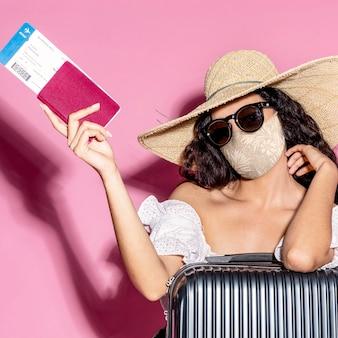 Turista en mascarilla con pasaporte y equipaje.