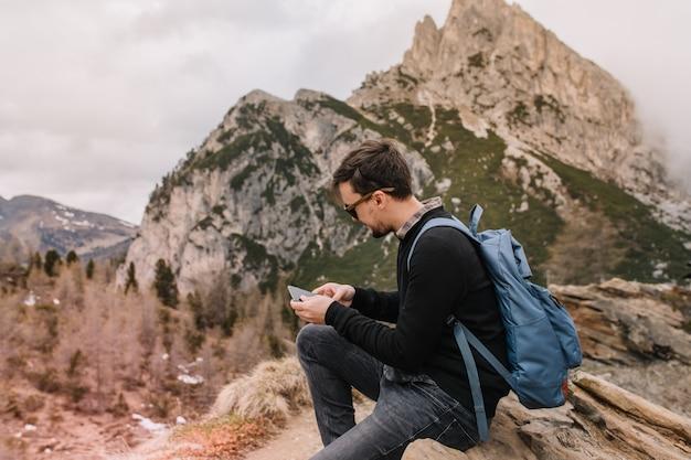 Turista masculino con cabello corto y oscuro descansando sobre piedra y mensaje de texto después de escalar montañas