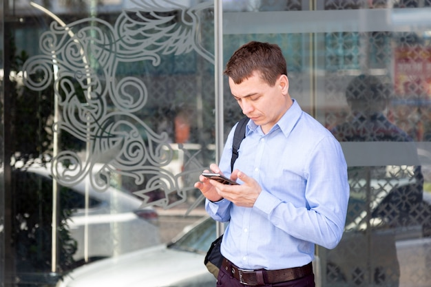 Turista masculino caucásico se comunica en las redes sociales en el teléfono inteligente mientras está de pie en una calle