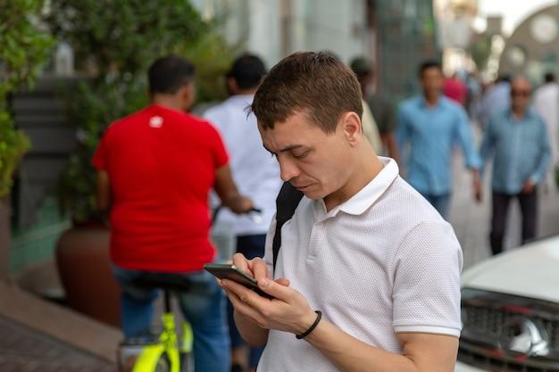 Turista masculino se comunica en las redes sociales en un teléfono inteligente mientras está parado en una calle en el distrito musulmán de la ciudad