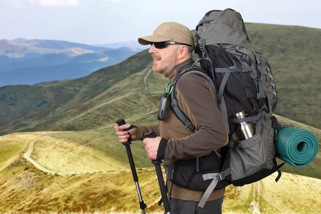 Turista masculino feliz con mochila está viajando en las tierras altas