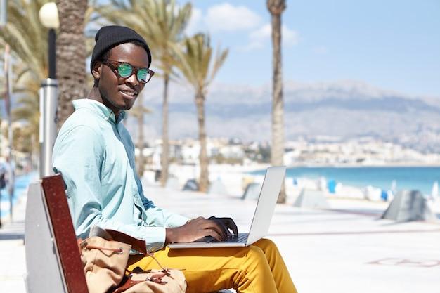 Turista masculino joven atractivo que se sienta en banco con el ordenador portátil