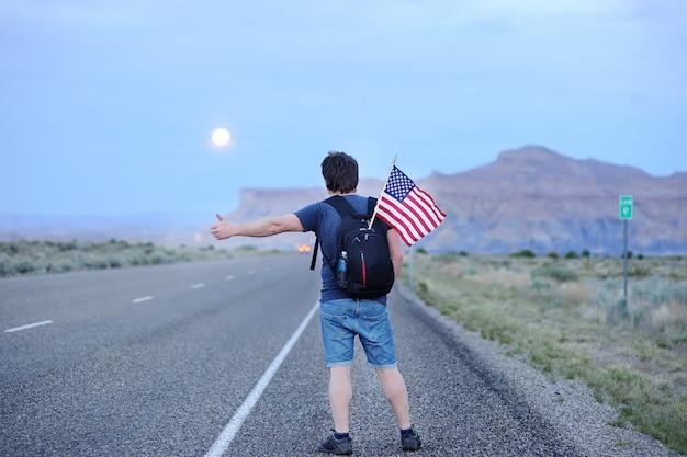 Turista masculino de mediana edad con bandera estadounidense en mochila haciendo autostop a lo largo de una carretera desolada