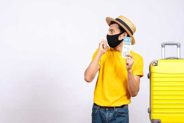 Turista masculino de la vista frontal con el sombrero de paja que se coloca cerca de la maleta amarilla que sostiene el boleto de avión