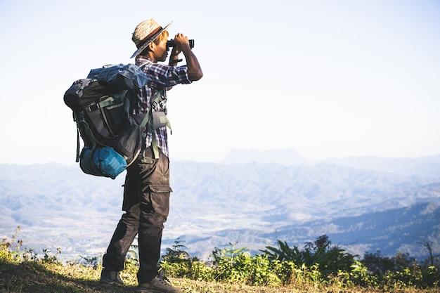 El turista está mirando a través de los prismáticos en el cielo nublado soleado desde la cima de la montaña.