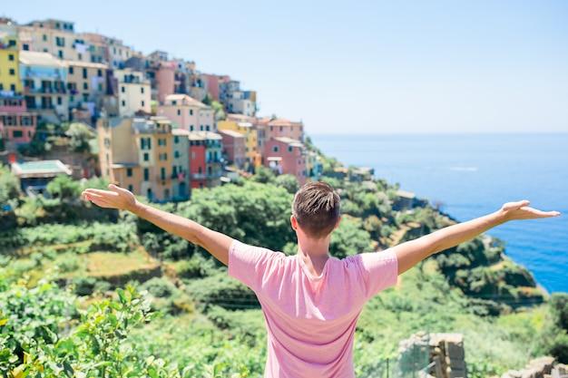 Turista mirando la vista panorámica de manarola, cinque terre, liguria, italia
