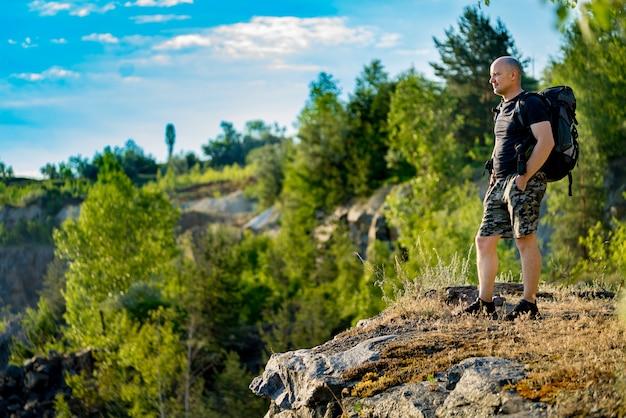 Turista con una mochila sobre sus hombros se para sobre una roca