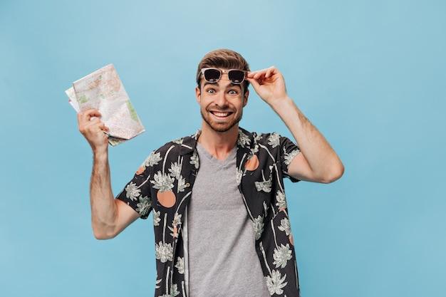 Turista de moda alegre en camiseta gris, camisa estampada y gafas de sol mirando al frente y sosteniendo el mapa en la pared aislada