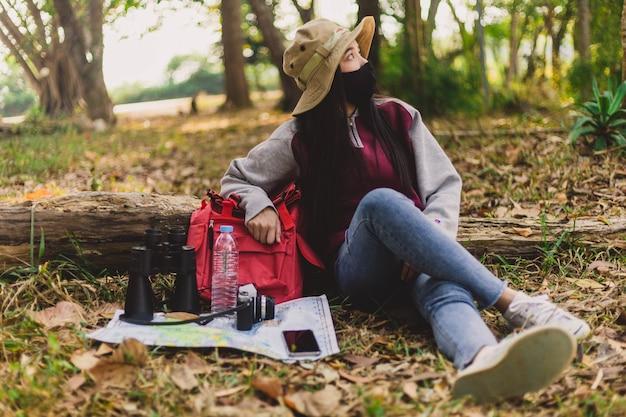Turista de mujer asiática con mascarilla sentado y descansando.