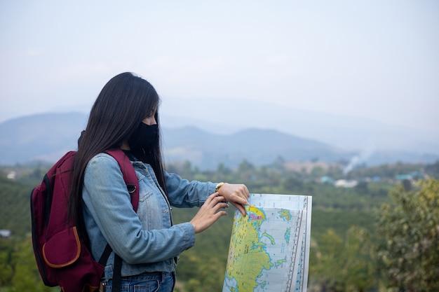 Turista mujer asiática vistiendo mascarilla mirando el reloj de pulsera