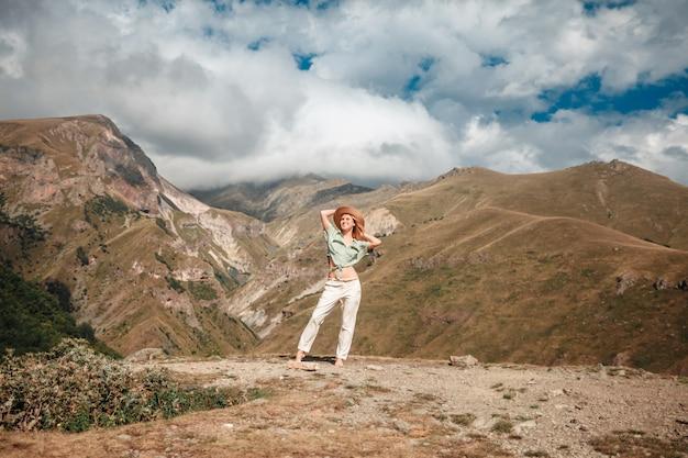 Turista de mujer de estilo de vida de viaje al aire libre posando en las montañas y el cielo nublado.