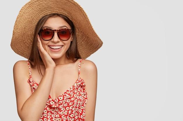 Turista de mujer feliz emocional complacido en elegante sombrero, ropa de verano