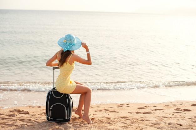 Turista de la mujer que se sienta cerca del mar en la maleta