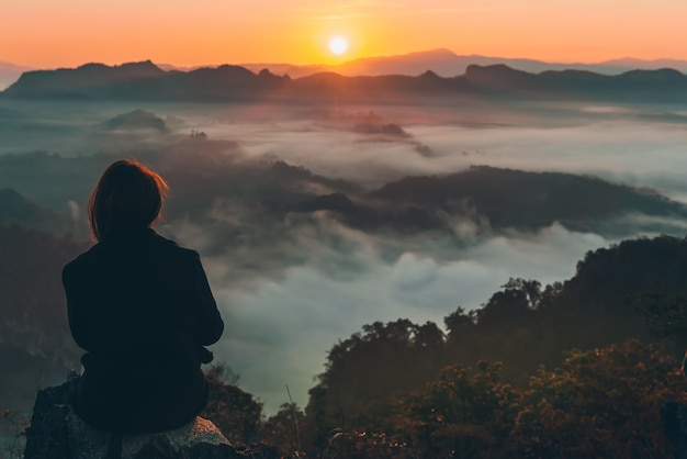 Turista de mujer está sentada en una montaña rocosa, mirando lo hermoso del amanecer y la niebla