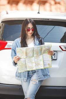 Turista mujer sosteniendo un mapa de la ciudad. viajero en coche navegando en el país desconocido. chica conduciendo un automóvil.