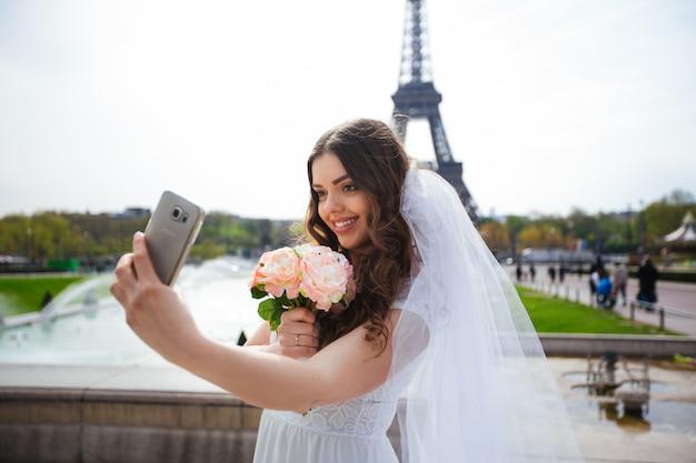 Turista de la mujer en la torre eiffel sonriendo y haciendo viajes selfie. hermosa chica europea disfrutando de vacaciones en parís, francia