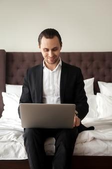 Turista de negocios trabajando en la computadora portátil en la habitación del hotel