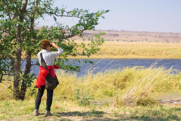 Turista observando la vida silvestre por binoculares en el río chobe, namibia botswana frontera, áfrica. el parque nacional chobe, la famosa reserva wildlilfe y un destino turístico exclusivo.