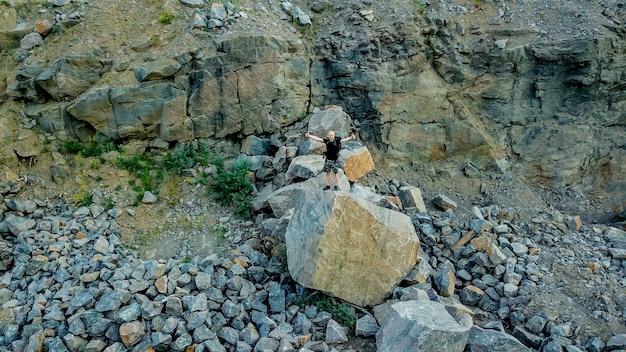 Un turista está parado sobre una gran piedra con las manos cerca de la roca.
