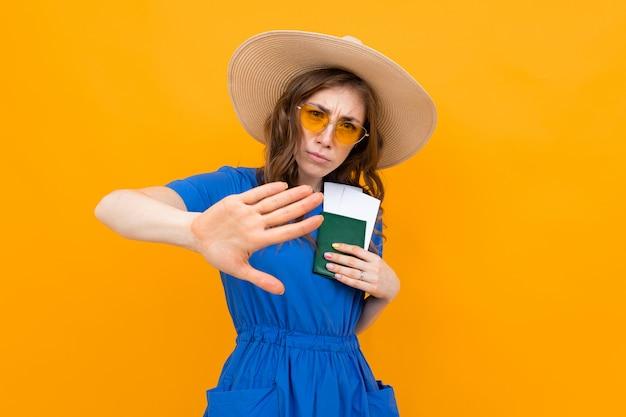 Turista con un pasaporte y boletos en sus manos sobre un fondo amarillo, un gesto muestra caer detrás de ella