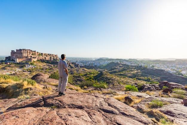 Turista de pie sobre una roca y mirando la vista expansiva del fuerte de jodhpur desde arriba, encaramado en la parte superior dominando la ciudad azul. destino de viaje en rajasthan, india.