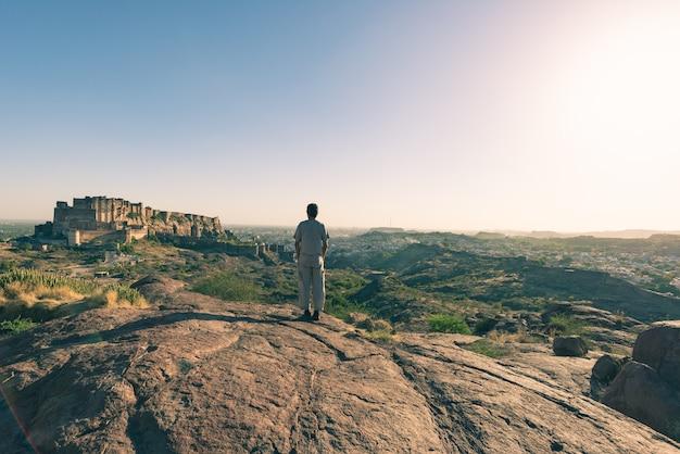 Turista de pie sobre una roca y mirando la vista expansiva del fuerte de jodhpur desde arriba