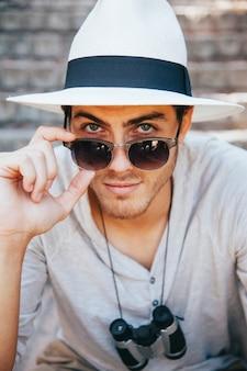 Turista posando con gafas de sol y prismáticos