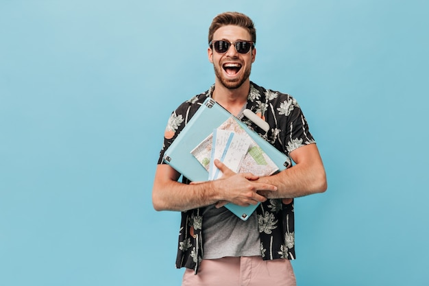 Turista positivo en gafas de sol frescas y camisa negra de verano con maleta azul, mapa y boletos de avión y se regocija en una pared aislada