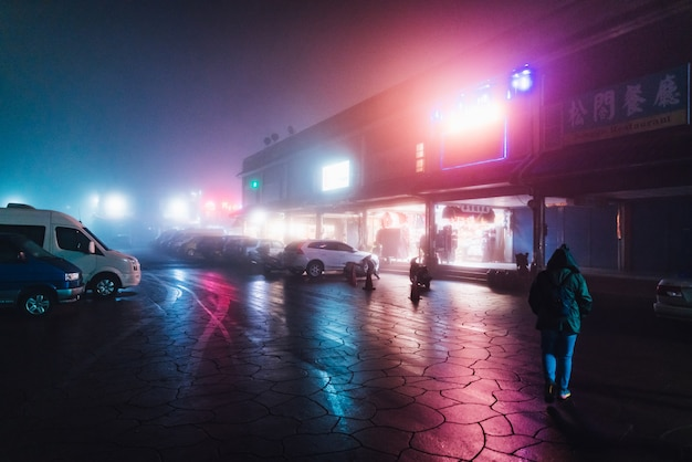 Turista que camina en la calle en la noche con niebla y luces coloridas del edificio en invierno en alishan, taiwán.