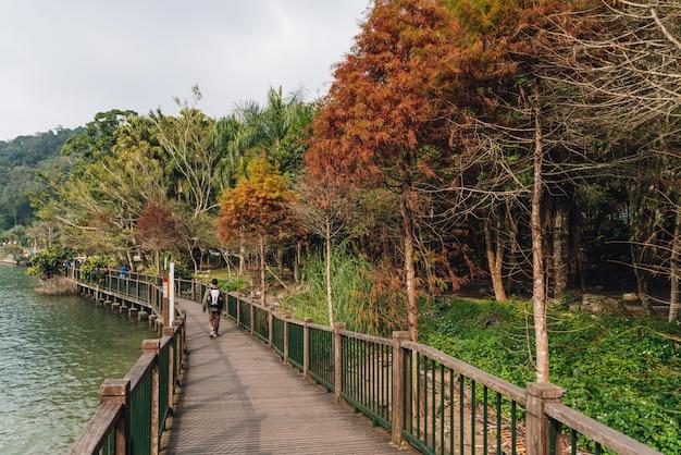Turista que camina en el camino de madera a lo largo del lado con sun moon lake.