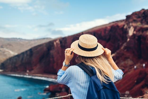 Turista que mira paisaje rojo de la playa desde el punto de vista en akrotiri, isla de santorini, grecia. mujer viajando