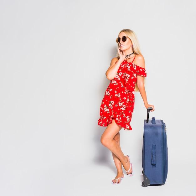 Turista rubia posando con maleta