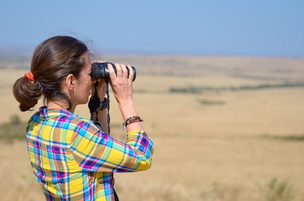 Turista en safari en áfrica, observando la vida salvaje de la sabana africana con binoculares