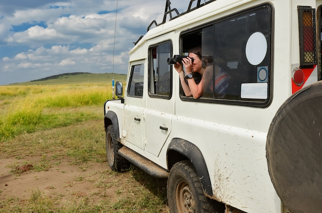 Turista en safari en áfrica, viajar a kenia, observar la vida silvestre en la sabana con binoculares