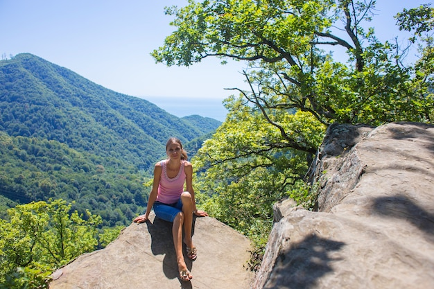 Turista se sienta en un acantilado de alta montaña en el contexto de la hermosa naturaleza y el mar